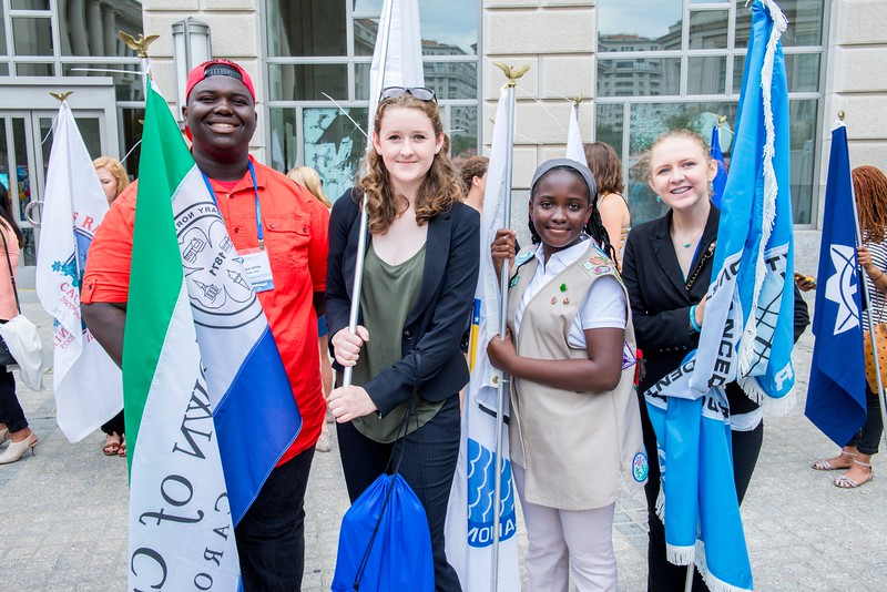 Students and girl scouts act as flag bearers during the