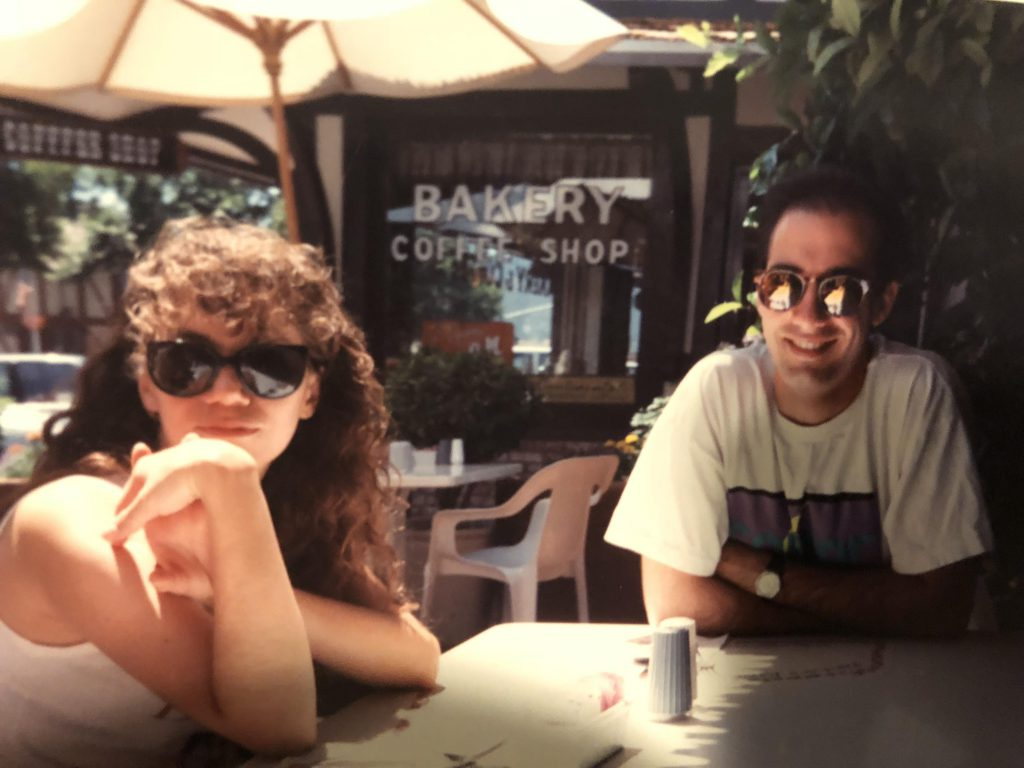 Roxanne Ornelas (on left) and Kris Haltmeyer (on right) seated at an outdoor cafe table in 1991
