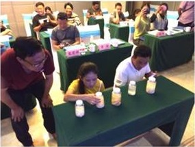 Trainees kneel while examining different species of tapeworms at table