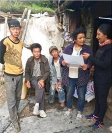Dr. Tsering Yangzom, medical doctor, Dongla Village, Shuiluo Township, educating local residents about NCC with the two laminated photo sheets that she received at the training in Xichang