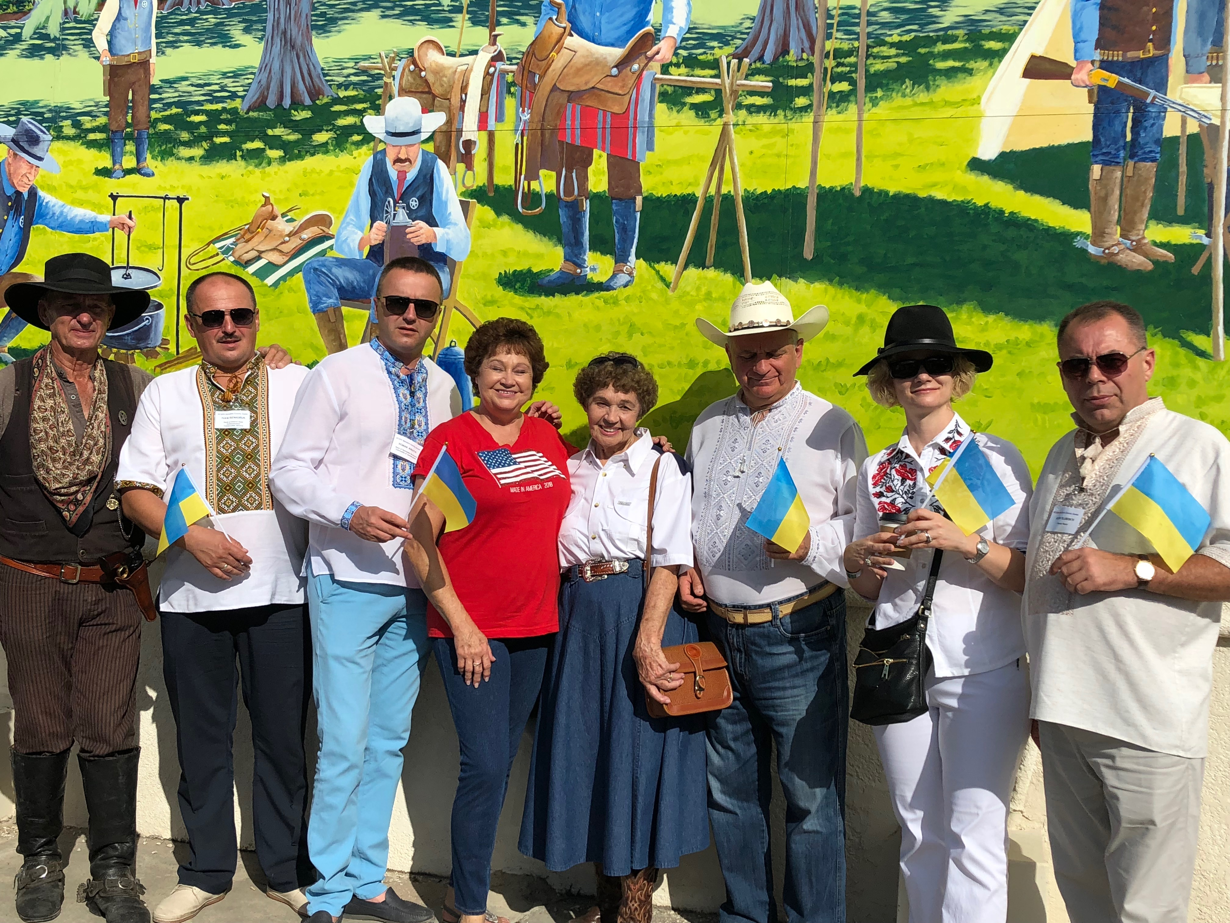 Delegation and volunteers pose in front of a mural