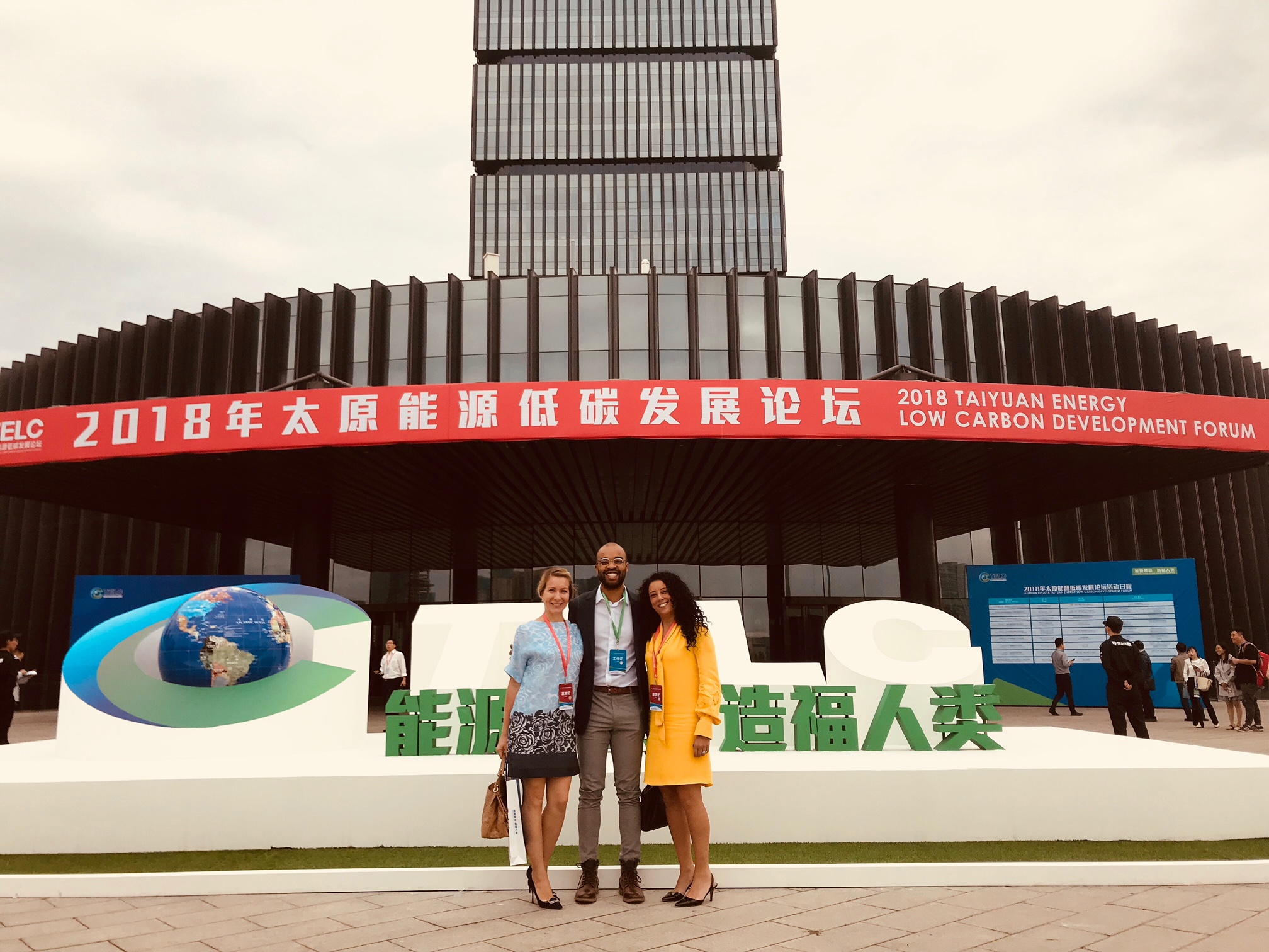 Three people pose in front of Chinese convention center