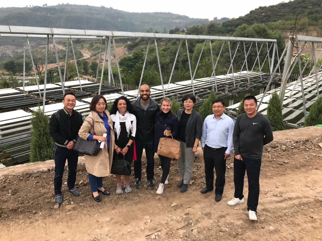 a group of eight poses in front of a solar farm on a Chinese hillside