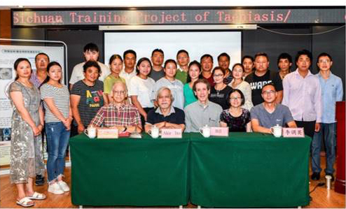 Picture of trainers and trainees in Xichang in front of table