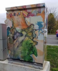 Utility box wrapped with laminate decal displaying a painting