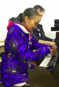 Young lady and man wearing jackets and playing piano